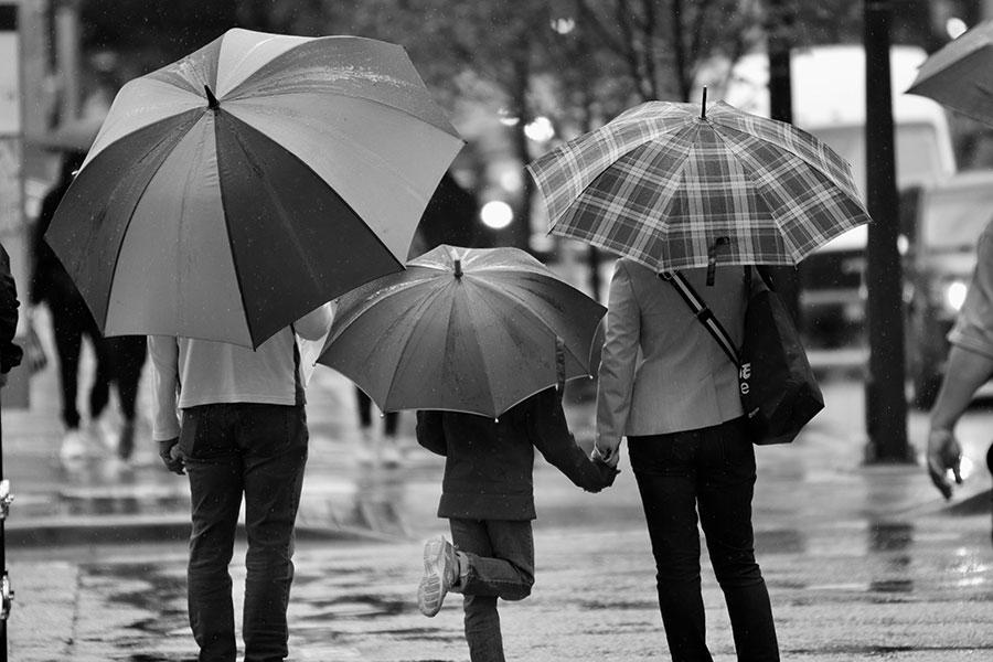 Coppia con bambino sotto la pioggia